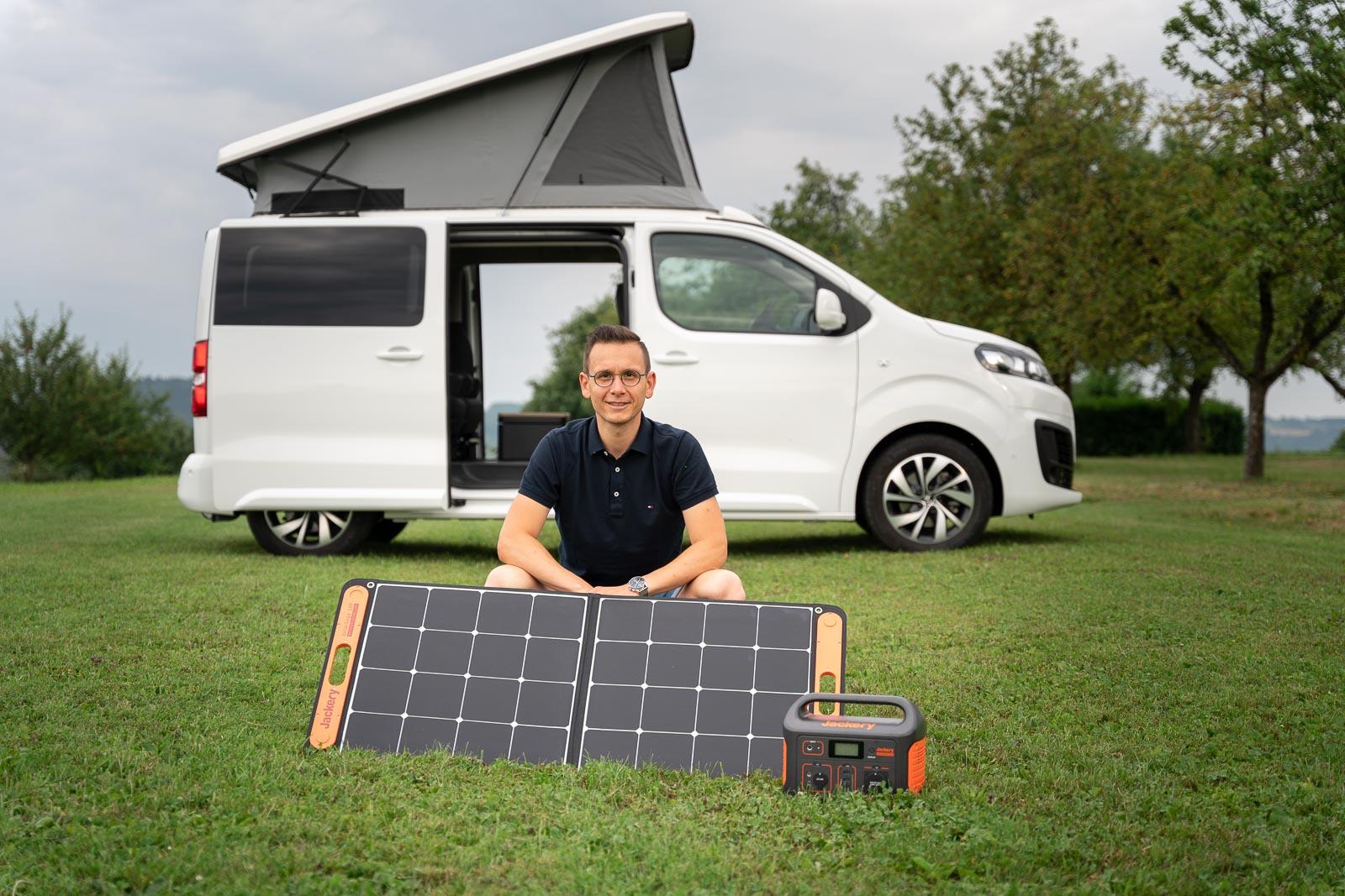 Solarmodul und Batterie vor einem Camper Van